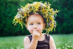 Pequeño bebé feliz hermoso en una guirnalda en un prado en la naturaleza imagenes de archivo
