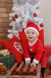 Pequeño bebé feliz lindo en el traje de Papá Noel en viejo ingenio del trineo del vintage Fotografía de archivo