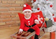 Pequeño bebé feliz lindo en el traje de Papá Noel en viejo ingenio del trineo del vintage Imagen de archivo