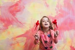 Pequeño bebé feliz que lleva a cabo corazones rojos decorativos del día de tarjetas del día de San Valentín Fotografía de archivo