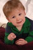 Pequeño bebé feliz que señala en la cámara Imagen de archivo libre de regalías