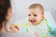 Pequeño bebé hambriento que come las frutas guisadas Imagen de archivo