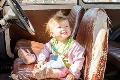 Pequeño bebé hermoso de la muchacha que se sienta en un viejo asiento de cuero permeable detrás de la rueda de un coche retro del Fotografía de archivo libre de regalías