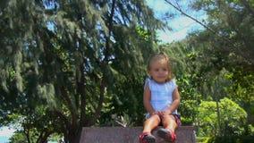 Pequeño bebé hermoso que está sin hacer nada en un pedestal y miradas del granito ella sonríe y se endereza el pelo En los árbole almacen de metraje de vídeo