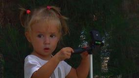 Pequeño bebé hermoso que juega con el trípode en el fondo de árboles almacen de metraje de vídeo