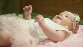 Pequeño bebé hermoso que miente en la cama almacen de metraje de vídeo