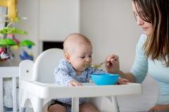 Pequeño bebé lindo, comiendo las verduras trituradas para el almuerzo, FE de la mamá fotografía de archivo libre de regalías