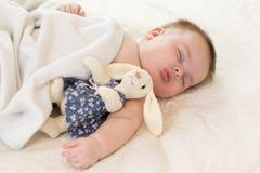 Pequeño bebé lindo con el juguete que duerme en cama en casa foto de archivo