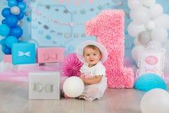 Pequeño bebé lindo con los ojos azules grandes que llevan el sombrero y la flor del tutú en su pelo que plantea sentarse en decor fotografía de archivo