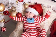 Pequeño bebé lindo de Papá Noel que presenta al lado del árbol de navidad en el hogar acogedor con la decoración del Año Nuevo Imagenes de archivo