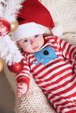 Pequeño bebé lindo de Papá Noel que presenta al lado del árbol de navidad en el hogar acogedor con la decoración del Año Nuevo Foto de archivo