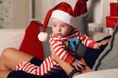 Pequeño bebé lindo de Papá Noel que se sienta en las manos de la mamá en el hogar acogedor con la decoración del Año Nuevo Imagen de archivo