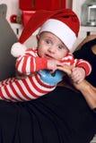Pequeño bebé lindo de Papá Noel que se sienta en las manos de la mamá en el hogar acogedor con la decoración del Año Nuevo Foto de archivo libre de regalías