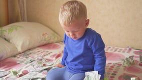 Pequeño bebé lindo debajo de una lluvia del dólar en cama Concepto de herencia almacen de video