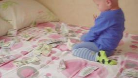 Pequeño bebé lindo debajo de una lluvia del dólar en cama Concepto de herencia metrajes