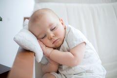 Pequeño bebé lindo, durmiendo en butaca con poca almohada, c imagen de archivo libre de regalías