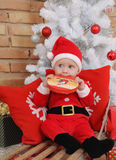 Pequeño bebé lindo en el traje de Papá Noel en el trineo viejo del vintage con el regalo Foto de archivo