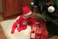 Pequeño bebé lindo feliz en Santa& x27; traje de s cerca del adornamiento del árbol de Navidad Fotografía de archivo