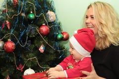 Pequeño bebé lindo feliz en Santa& x27; traje de s cerca del adornamiento del árbol de Navidad Foto de archivo libre de regalías