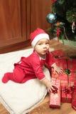 Pequeño bebé lindo feliz en Santa& x27; traje de s cerca del adornamiento del árbol de Navidad Foto de archivo