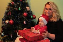 Pequeño bebé lindo feliz en Santa& x27; traje de s cerca del adornamiento del árbol de Navidad Imágenes de archivo libres de regalías
