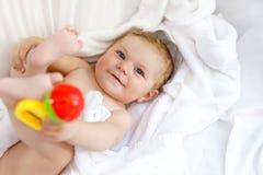 Pequeño bebé lindo que juega con traqueteo del juguete y poseer pies después de tomar el baño Muchacha hermosa adorable envuelta  Imagen de archivo libre de regalías