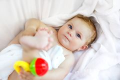 Pequeño bebé lindo que juega con traqueteo del juguete y poseer pies después de tomar el baño Muchacha hermosa adorable envuelta  Fotos de archivo libres de regalías