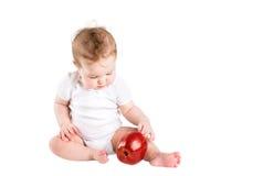 Pequeño bebé lindo que juega con una manzana roja grande Fotografía de archivo