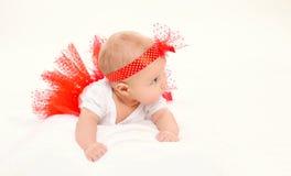 Pequeño bebé lindo que miente en falda roja Imagen de archivo