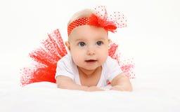 Pequeño bebé lindo que miente en falda roja en cama Imagen de archivo