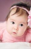 Pequeño bebé lindo que miente en la cama en vestido rosado Foto de archivo libre de regalías