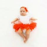 Pequeño bebé lindo que miente en la falda roja Foto de archivo libre de regalías