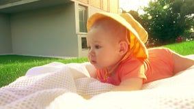 Pequeño bebé lindo que pone en la toalla en la hierba almacen de metraje de vídeo