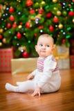Pequeño bebé lindo que se sienta delante del árbol de navidad Imagen de archivo libre de regalías