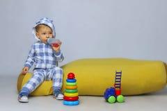 Pequeño bebé lindo que se sienta en Bean Bag Chair amarillo y que juega los juguetes Fotografía de archivo libre de regalías