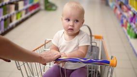 Pequeño bebé lindo que se sienta en un carro del ultramarinos en un supermercado que mira alrededor El ` s de la madre da empujar