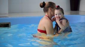 Pequeño bebé lindo y su madre que tienen lección que nada en la piscina La madre está celebrando a su hijo en sus manos y almacen de metraje de vídeo