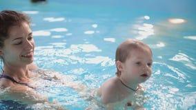 Pequeño bebé lindo y su madre que tienen lección que nada en la piscina La madre está celebrando a su hijo en sus manos y metrajes