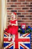 Pequeño bebé muy lindo en un vestido rojo que ríe y que lleva a cabo un cand imágenes de archivo libres de regalías