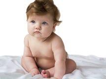 Pequeño bebé pensativo que se sienta en un pañal Imagenes de archivo