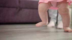 Pequeño bebé que aprende el paseo en piso Niño que hace los primeros pasos con el padre almacen de video