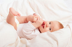Pequeño bebé que chupa su dedo en la pierna Fotos de archivo libres de regalías