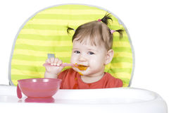 Pequeño bebé que come un puré vegetal Imagenes de archivo