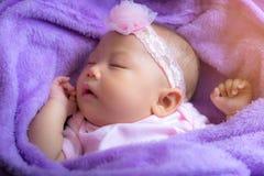 Pequeño bebé que duerme en pesebre púrpura imagen de archivo libre de regalías