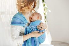 Pequeño bebé que duerme firmemente con la boca abierta y la expresión dulce de la cara en honda del bebé mientras que mamá que de imágenes de archivo libres de regalías