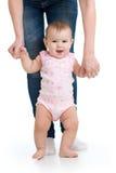 Pequeño bebé que hace los primeros pasos con la ayuda de la madre fotografía de archivo libre de regalías