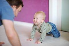 Pequeño bebé que juega con su padre Foto de archivo libre de regalías