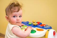 Pequeño bebé que juega en un piano del juguete Foto de archivo