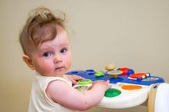 Pequeño bebé que juega en un piano del juguete Foto de archivo libre de regalías