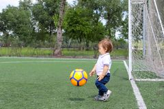 Pequeño bebé que juega a fútbol en campo de fútbol Fotos de archivo
